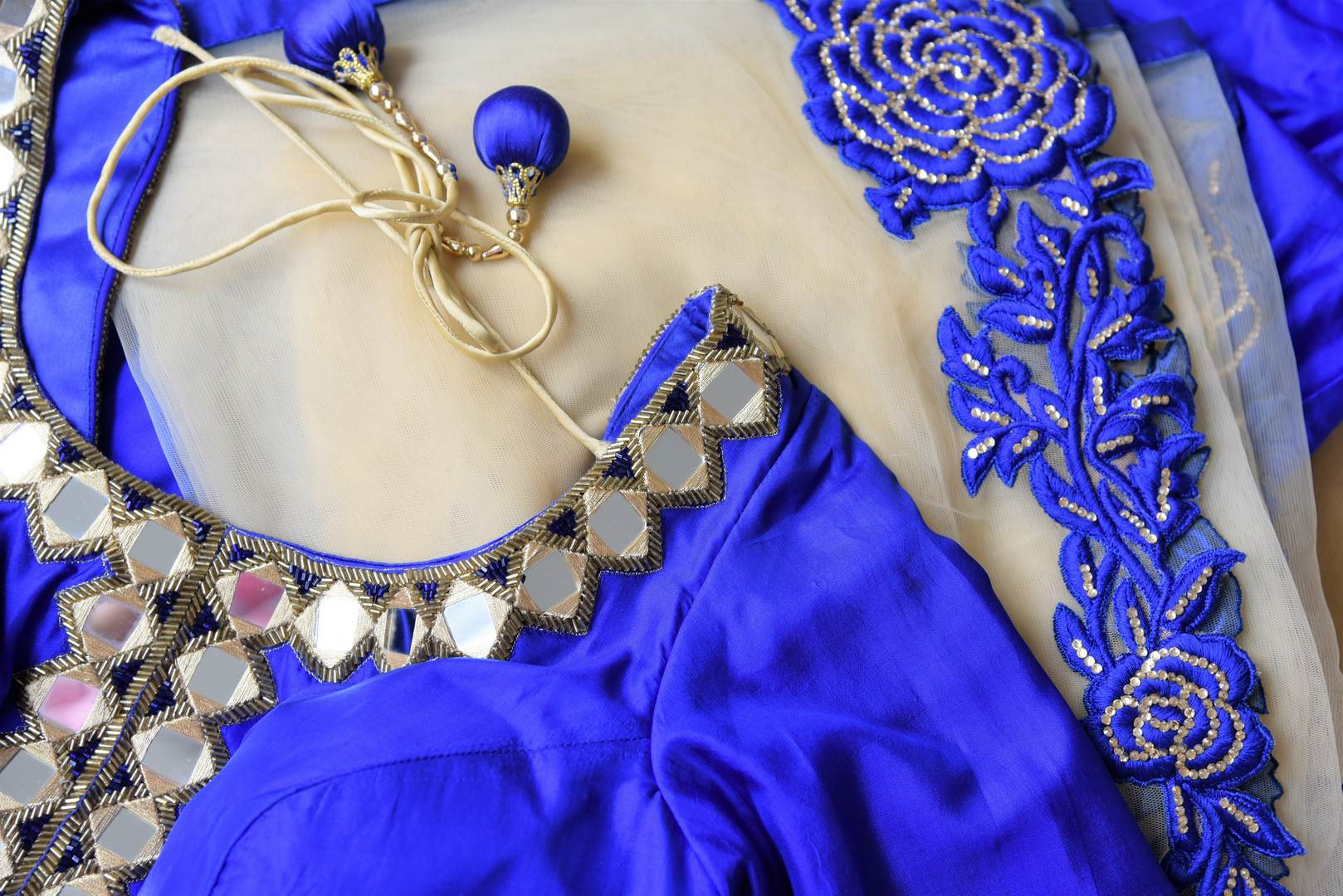Slay effortlessly in this electric blue silk mirror work embroidered Anarkali suit with beige sheer net dupatta. The gorgeous embroidery on the border of dupatta and gold zari border on the hem of the suit looks scintillating. Shop beautiful Indian dresses, suits, sarees online or visit Pure Elegance store, USA. -details