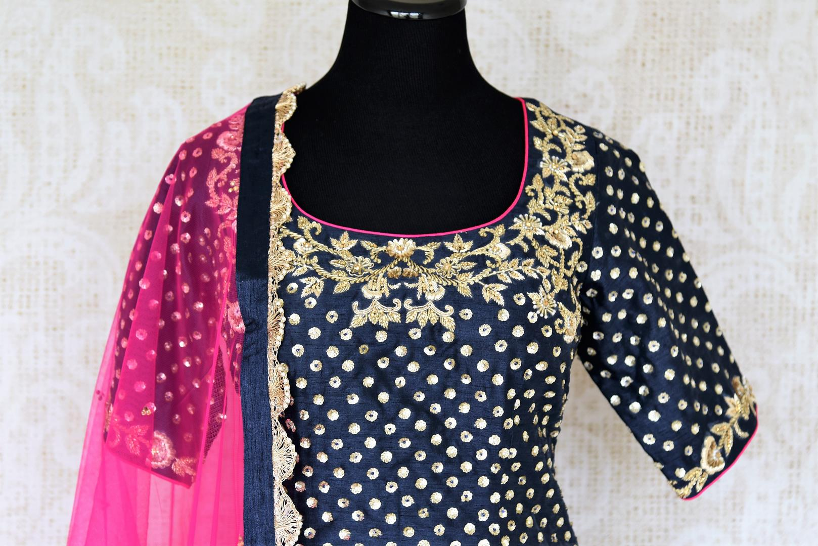 The Bollywood-inspired black raw silk embellished sharara with blue embroidered kurta is your go-to for weddings, festivals and family gatherings. Complete the look with a contrasting pink embellished sheer dupatta. Shop beautiful Indian designer dresses, suits, lehengas, online or visit Pure Elegance store, USA. -suit front