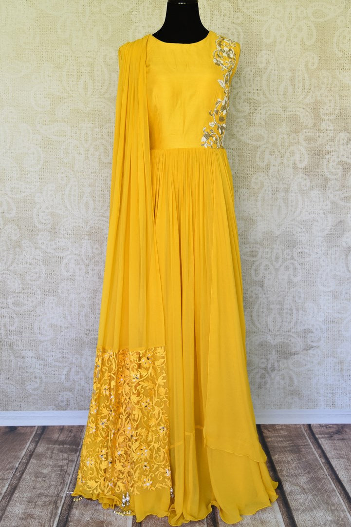 The gorgeous bright yellow floor-length georgette dress is a sight to behold. The floral embroidery on silk upper crest of this dress is well complemented with a falling drape on the side. Shop designer lehenga sets, salwar suits, sarees online or visit Pure Elegance store, USA. -full view