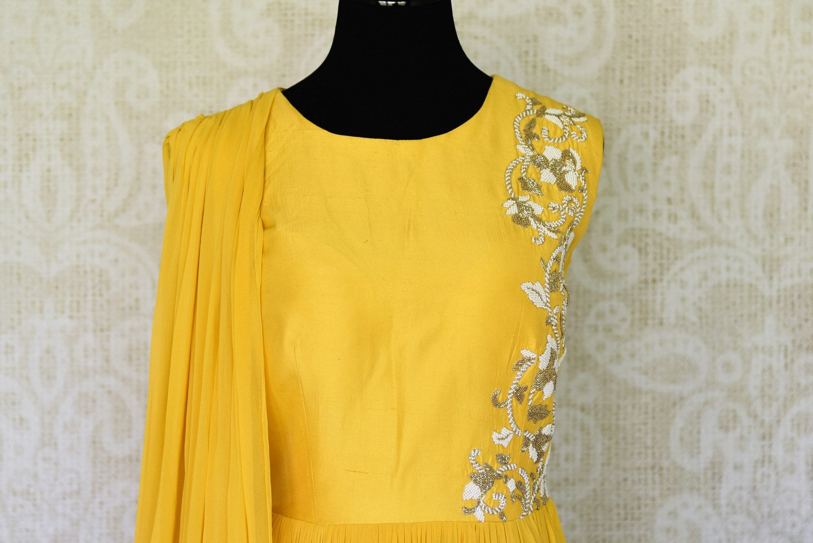 The gorgeous bright yellow floor-length georgette dress is a sight to behold. The floral embroidery on silk upper crest of this dress is well complemented with a falling drape on the side. Shop designer lehenga sets, salwar suits, sarees online or visit Pure Elegance store, USA. -front view
