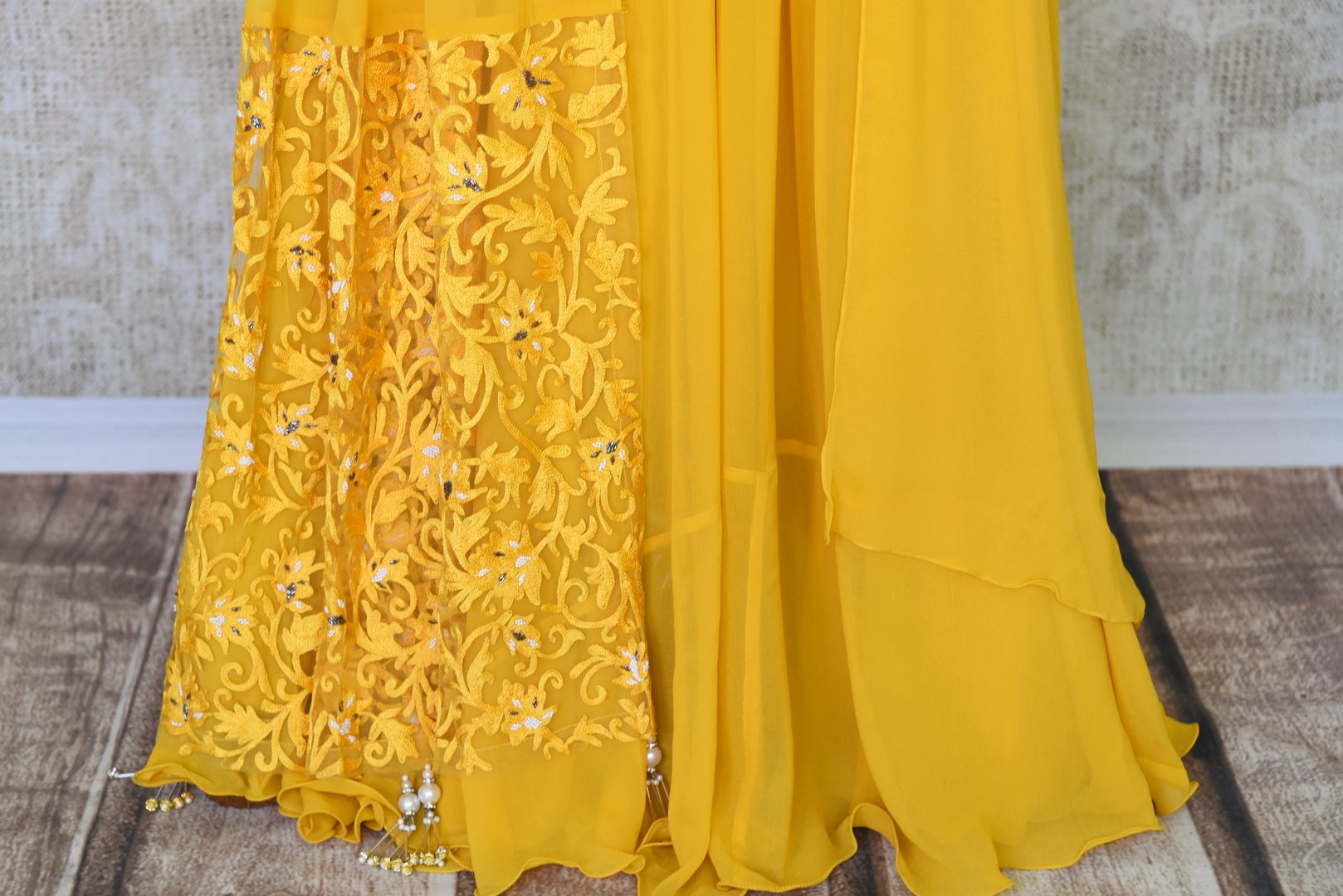 The gorgeous bright yellow floor-length georgette dress is a sight to behold. The floral embroidery on silk upper crest of this dress is well complemented with a falling drape on the side. Shop designer lehenga sets, salwar suits, sarees online or visit Pure Elegance store, USA. -skirt