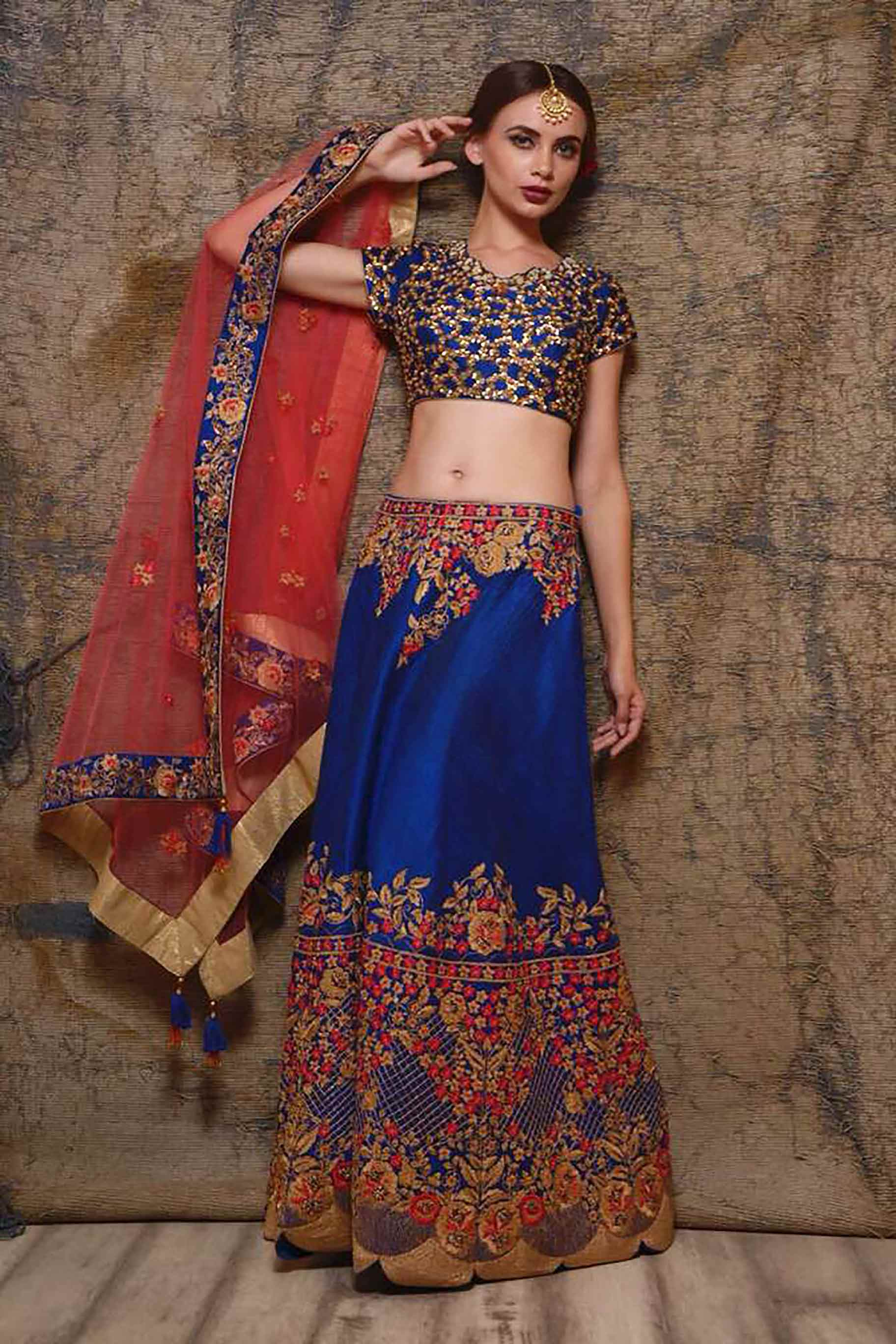 Buy blue raw silk embroidered lehenga online in USA with red net dupatta. Shine in rich silhouettes of exquisite Indian designer wedding lehengas from Pure Elegance Indian clothing store for women in USA or shop online.-full view
