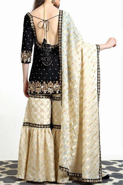 Buy black silk blend short kurta with ivory tissue net gharara online in USA. Get occasion ready with a stunning range of Indian designer suits from Pure Elegance fashion store in USA. We bring the best designer dresses for Indian women in USA at our online store. Shop now.-back