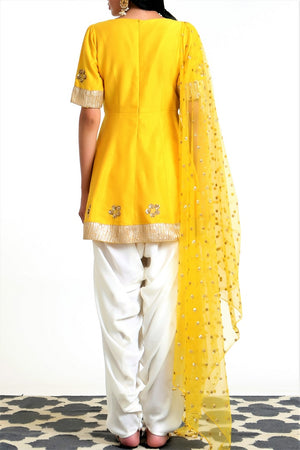 Buy yellow silk blend peplum kurta with white dhoti salwar and net dupatta online in USA. Get occasion ready with a stunning range of Indian designer suits from Pure Elegance fashion store in USA. We bring the best designer dresses for Indian women in USA at our online store. Shop now.-back