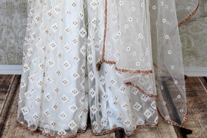 White embroidered net suit with palazzo for online shopping in USA. Get floored by a vibrant collection of Indian clothing at Pure Elegance Indian fashion store in USA. Choose from a beautiful range of Indian designer suits, Anarkalis, designer lehengas for weddings and special occasions.-palazzo