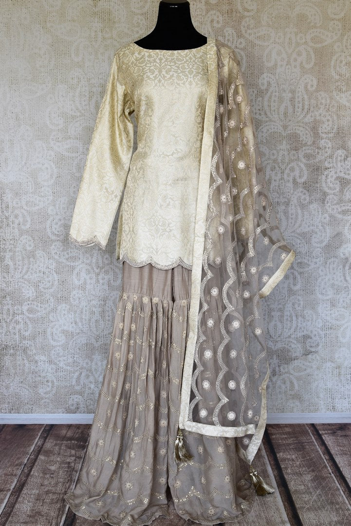 Shop cream embroidered Banarasi silk suit online in USA with grey silk sharara. Keep your wardrobe update with latest Indian clothing from Pure Elegance Indian fashion store in USA. Shop beautiful Indian designer lehengas, Anarkali suits, gowns for Indian women in USA from our online store.-full view