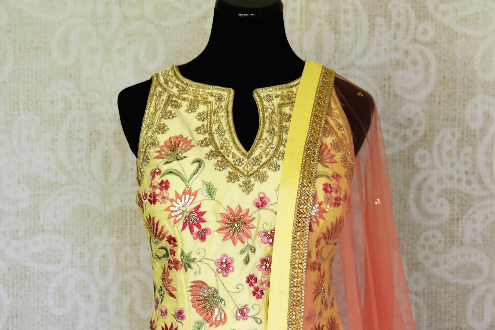 Shop gorgeous yellow embroidered net and silk sharara suit online in USA with pink dupatta. Step up your ethnic fashion game with exquisite variety of designer suits from Pure Elegance Indian clothing store in USA. Shop online.-top