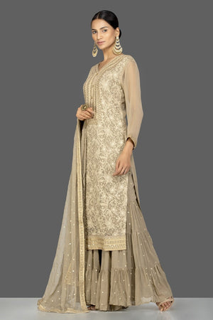Shop gorgeous beige embroidered georgette sharara suit online in USA with dupatta. Be an epitome of Indian fashion with a premium range of designer suits, Anarkali dresses from Pure Elegance luxury Indian fashion store in USA. Buy online now.-side