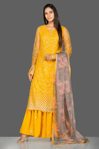 Shop lovely yellow embroidered net sharara suit online in USA with floral organza dupatta. Turn heads at weddings and festive occasions with exquisite Indian women designer clothes from Pure Elegance Indian fashion store in USA. Shop now.-full view
