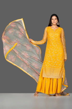 Shop lovely yellow embroidered net sharara suit online in USA with floral organza dupatta. Turn heads at weddings and festive occasions with exquisite Indian women designer clothes from Pure Elegance Indian fashion store in USA. Shop now.-front