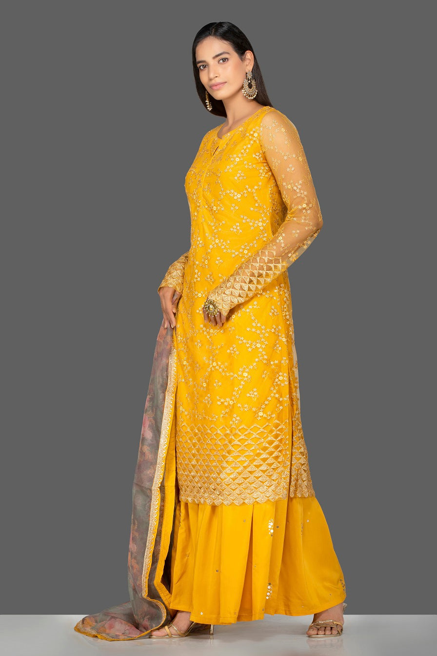 Shop lovely yellow embroidered net sharara suit online in USA with floral organza dupatta. Turn heads at weddings and festive occasions with exquisite Indian women designer clothes from Pure Elegance Indian fashion store in USA. Shop now.-side