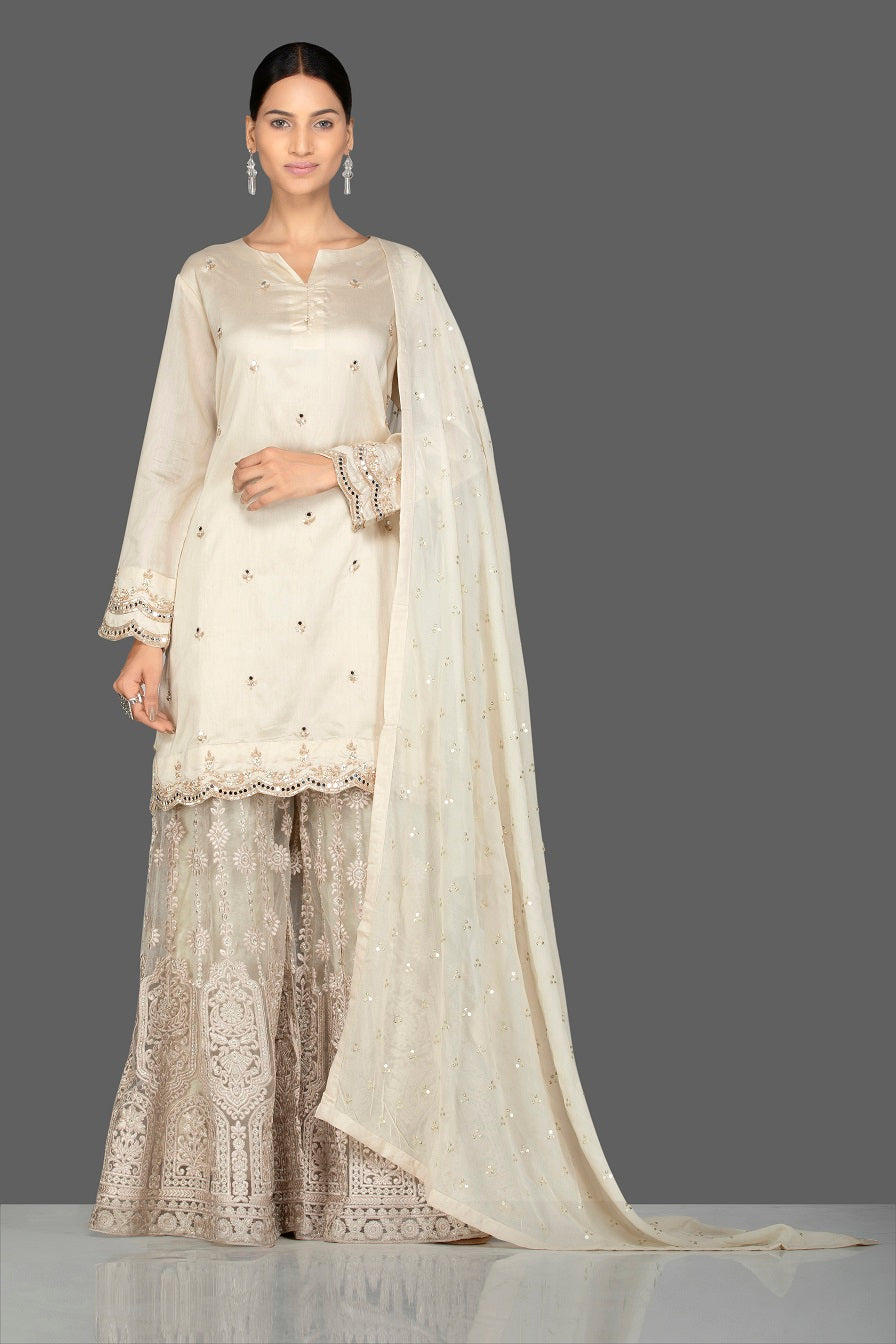 Shop stunning cream silk and net embroidered sharara suit online in USA with matching dupatta. Turn heads at weddings and festive occasions with exquisite Indian women designer clothes from Pure Elegance Indian fashion store in USA. Shop now.-full view