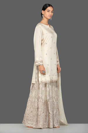 Shop stunning cream silk and net embroidered sharara suit online in USA with matching dupatta. Turn heads at weddings and festive occasions with exquisite Indian women designer clothes from Pure Elegance Indian fashion store in USA. Shop now.-side