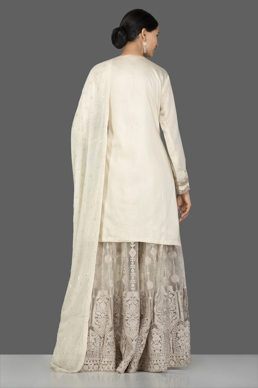 Shop stunning cream silk and net embroidered sharara suit online in USA with matching dupatta. Turn heads at weddings and festive occasions with exquisite Indian women designer clothes from Pure Elegance Indian fashion store in USA. Shop now.-back