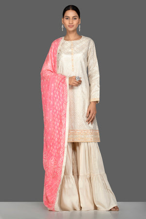 Buy gorgeous cream brocade and georgette sharara online in USA with pink bandhej dupatta. Turn heads at weddings and festive occasions with exquisite Indian women designer clothes from Pure Elegance Indian fashion store in USA. Shop now.-front