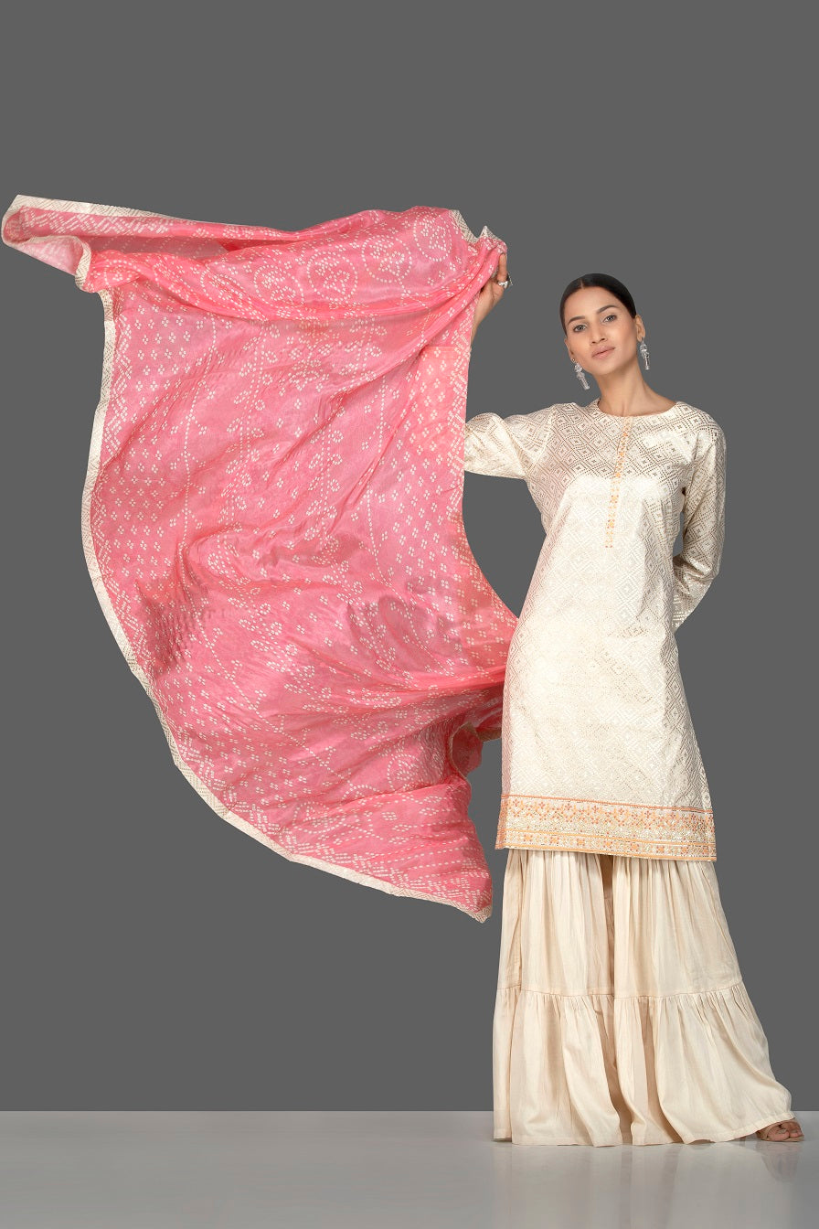 Buy gorgeous cream brocade and georgette sharara online in USA with pink bandhej dupatta. Turn heads at weddings and festive occasions with exquisite Indian women designer clothes from Pure Elegance Indian fashion store in USA. Shop now.-full view