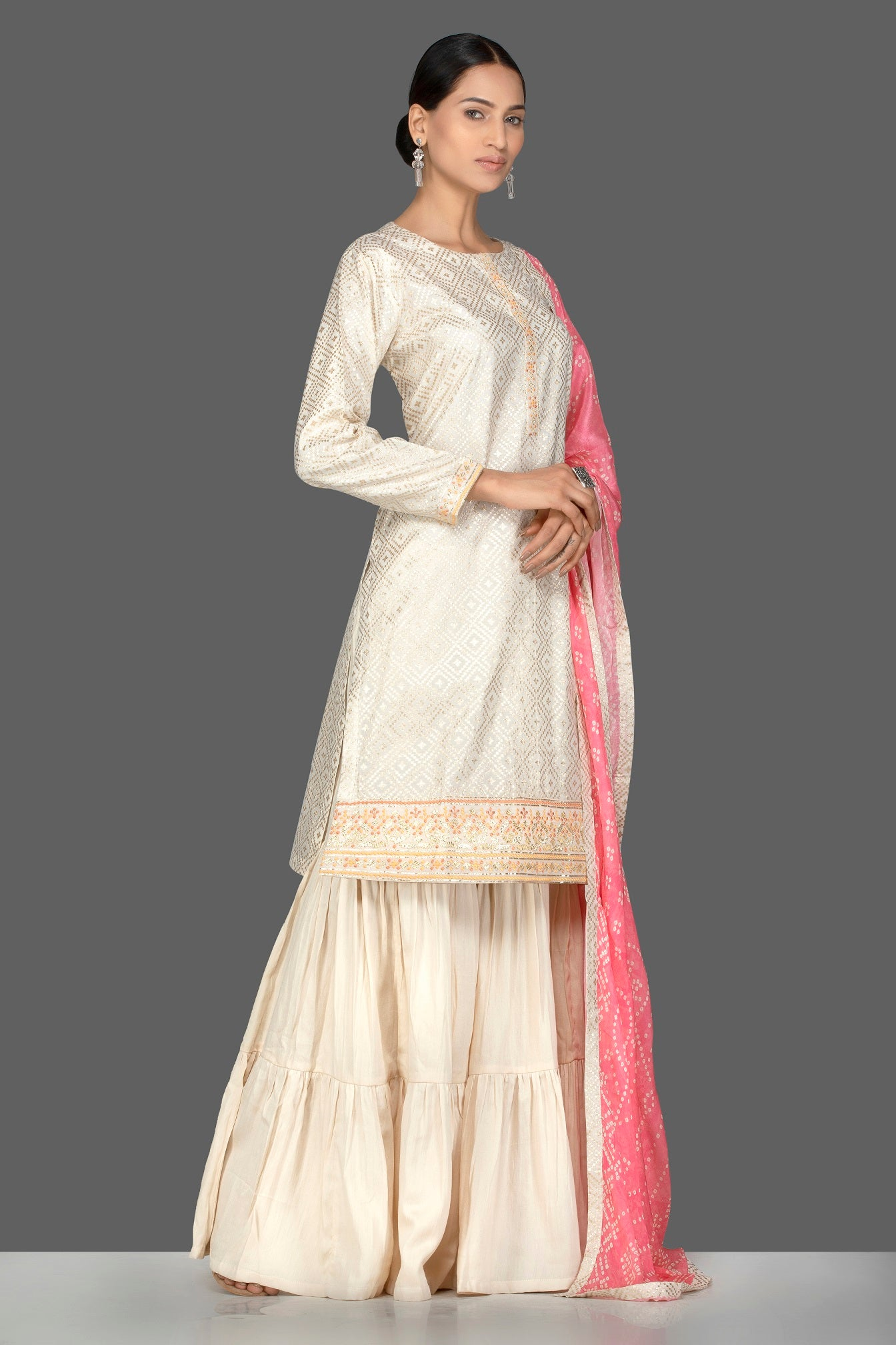Buy gorgeous cream brocade and georgette sharara online in USA with pink bandhej dupatta. Turn heads at weddings and festive occasions with exquisite Indian women designer clothes from Pure Elegance Indian fashion store in USA. Shop now.-side