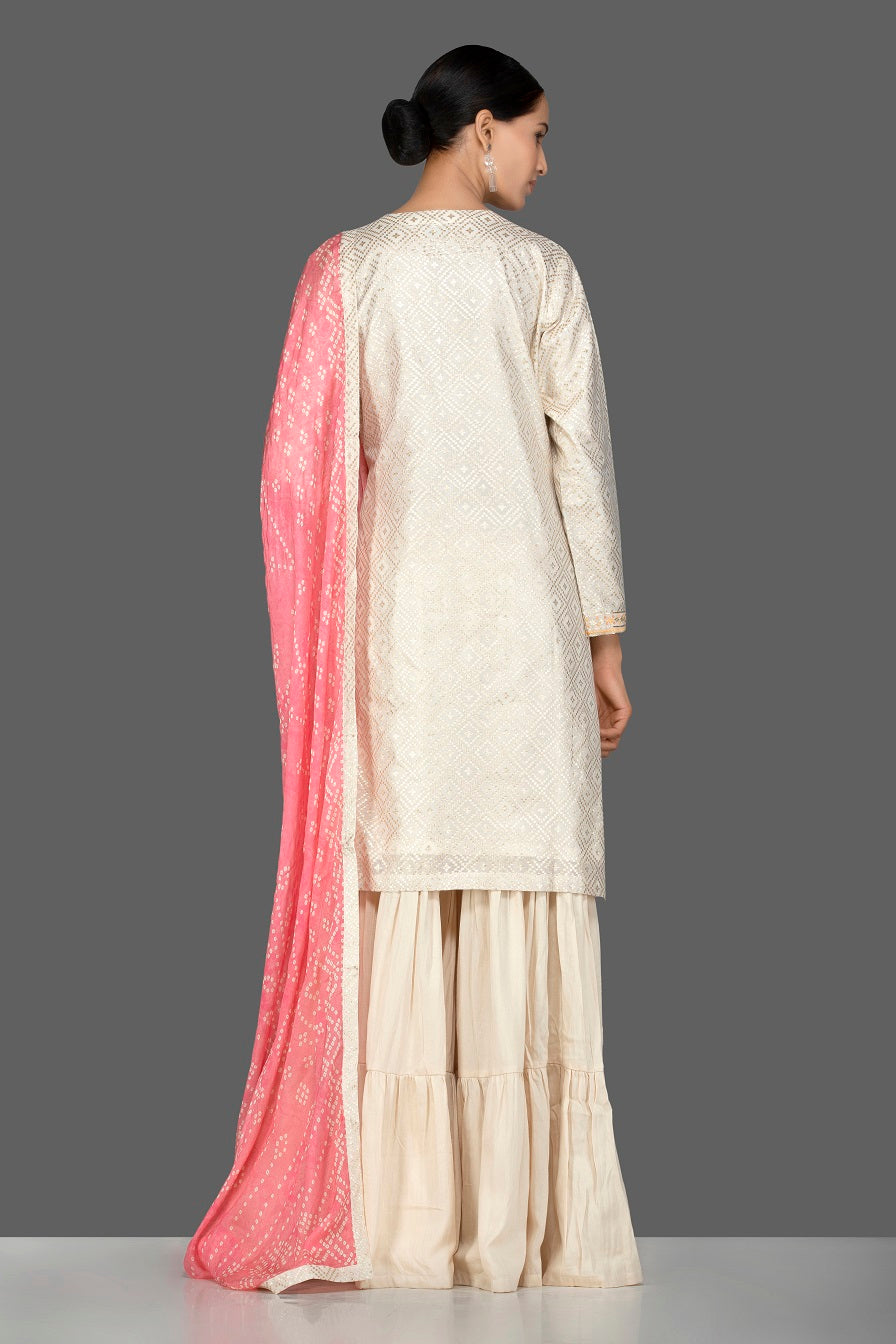 Buy gorgeous cream brocade and georgette sharara online in USA with pink bandhej dupatta. Turn heads at weddings and festive occasions with exquisite Indian women designer clothes from Pure Elegance Indian fashion store in USA. Shop now.-back