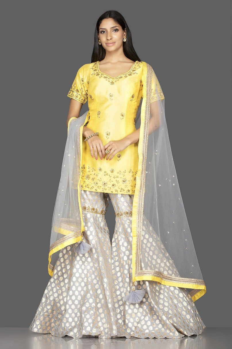 Shop beautiful yellow and grey embroidered cotton silk garara suit online in USA with dupatta. Spread ethnic elegance on weddings and special occasions in splendid designer lehengas, Anarkali suits crafted with exquisite Indian craftsmanship from Pure Elegance Indian fashion store in USA.-front