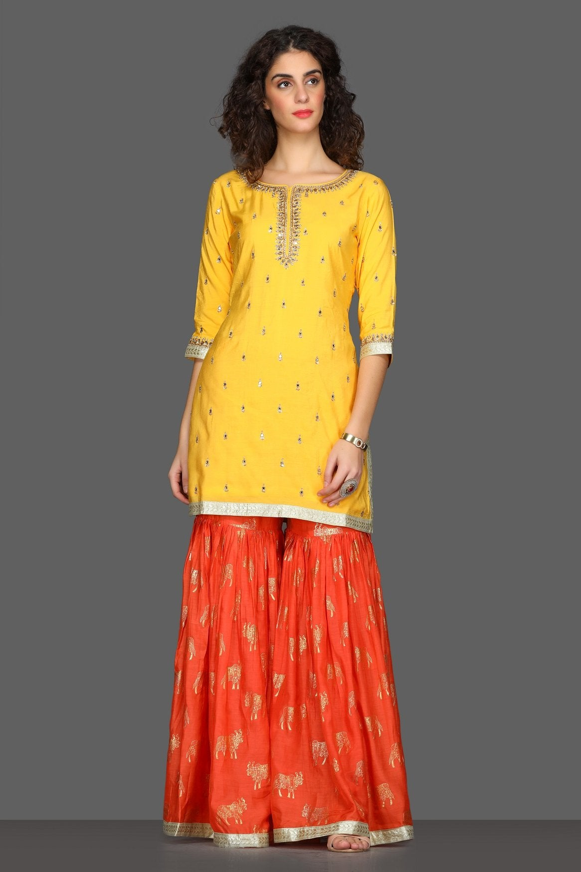 Buy bright yellow and red embroidered sharara suit online in USA with printed dupatta. Dazzle on weddings and special occasions with exquisite Indian designer dresses, sharara suits, Anarkali suits from Pure Elegance Indian fashion store in USA.-front