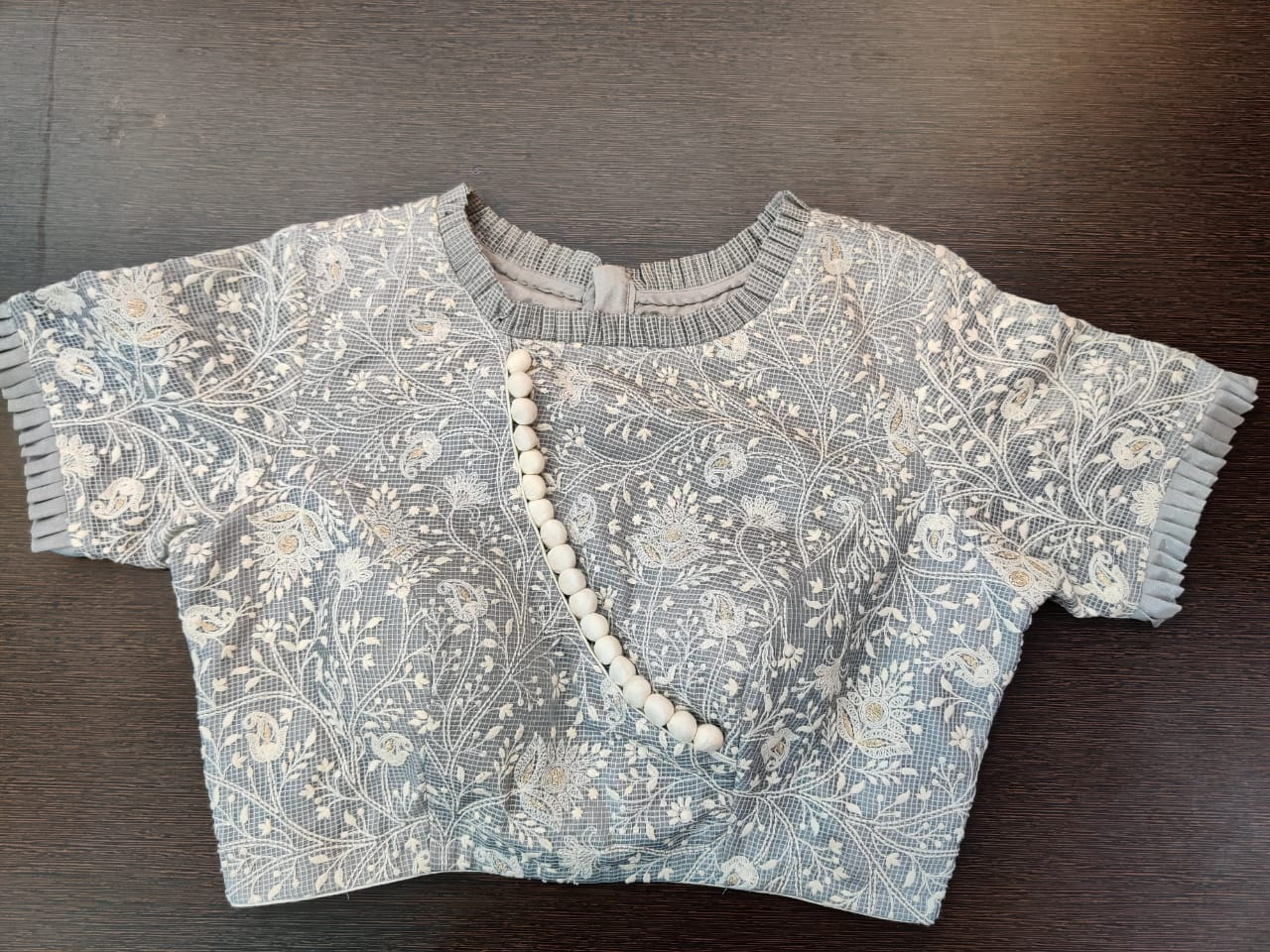 Shop grey embroidered saree blouse online in USA with frill edging. Elevate your Indian saree style with exquisite readymade sari blouses, embroidered saree blouses, Benarasi saree blouse, fancy saree blouse from Pure Elegance Indian clothing store in USA.-front