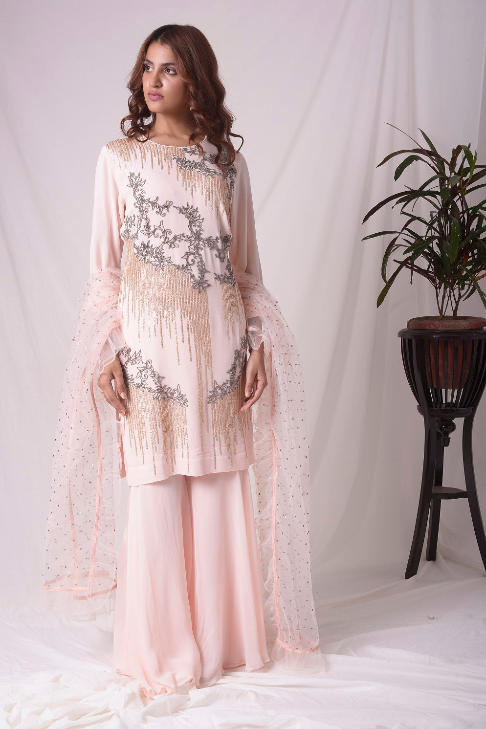 Buy pink georgette suit online in USA. Suit has gold and grey design work. Kurta has long sleeves. Suit had baby pink palazzo and pink net duppatta. Simple look makes it elegant. Be the talk of parties and weddings with exquisite designer gowns from Pure Elegance Indian clothing store in USA. Shop online now.-full view