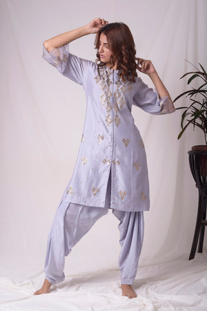 Buy lavender embroidered chanderi suit online in USA. Suit has simple golden work. Kurta has 3/4 length sleeves with net like at border, dhoti and rhombus neckline. Simple look makes it elegant. Be the talk of parties and weddings with exquisite designer gowns from Pure Elegance Indian clothing store in USA. Shop online now.-full view-4