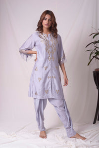 Buy lavender embroidered chanderi suit online in USA. Suit has simple golden work. Kurta has 3/4 length sleeves with net like at border, dhoti and rhombus neckline. Simple look makes it elegant. Be the talk of parties and weddings with exquisite designer gowns from Pure Elegance Indian clothing store in USA. Shop online now.-full view
