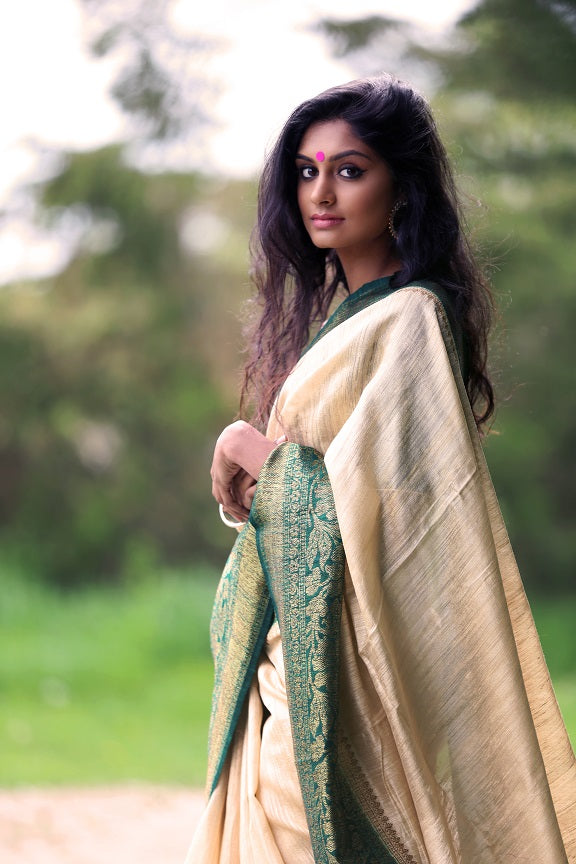 Shop beautiful off-white tussar Benarasi saree online in USA with green zari border. Set high fashion standard with your beautiful collection of Indian designer sarees from Pure Elegance. Pick your favorite pure silk saris, traditional Banarasi sarees, embroidered saris from our exclusive Indian clothing store in USA.-side view