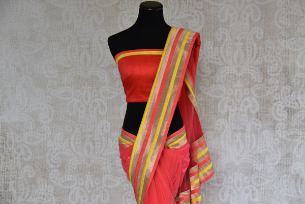 90A492 Coral red sari from India with multi-colored border & designer blouse. Buy this net saree, perfect for party wear, online at our Indian clothing store - Pure Elegance and get set to wow.