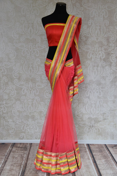 90A492 Coral red sari from India with multi-colored border & designer blouse. Buy this net saree, perfect for party wear, online at our Indian fashion store in USA - Pure Elegance.