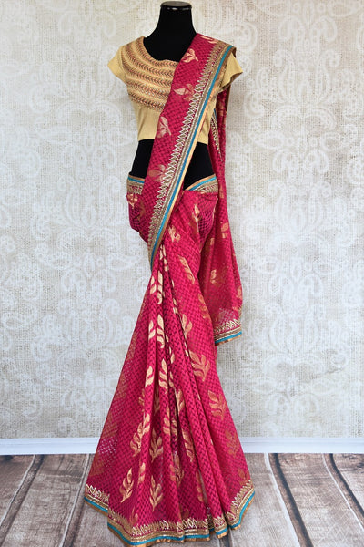 90a621 Traditional pink embroidered saree for sale online in USA. The jute Banarasi saree with golden leafy pattern comes with a beige, embroidered raw silk designer blouse. This saree makes for the perfect Indian outfit to wear at small wedding function.
