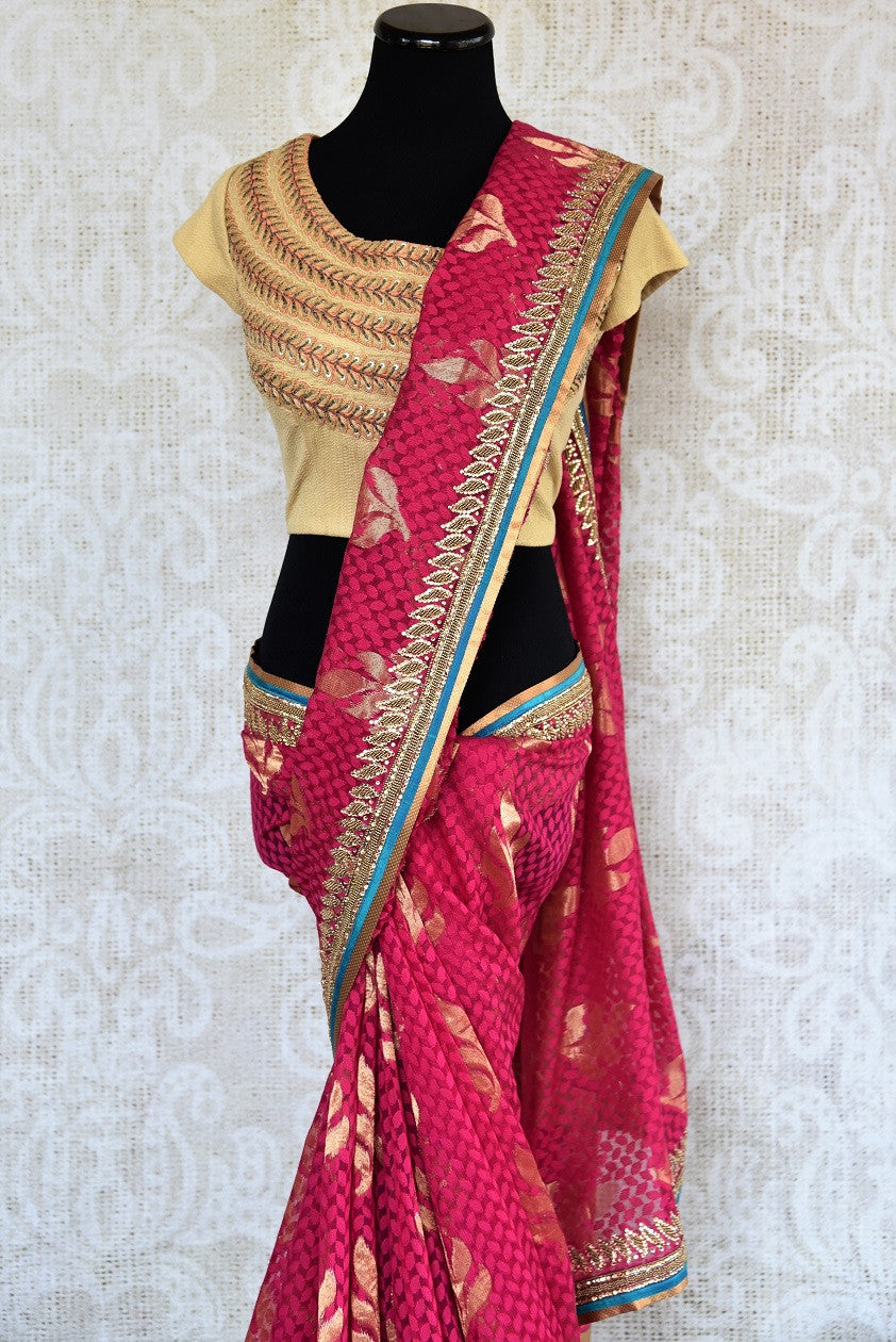90a621 Traditional pink embroidered saree for sale online in USA. The jute Banarasi saree with golden leafy pattern comes with a beige, embroidered raw silk designer blouse. This saree makes for the perfect Indian outfit to wear at wedding functions and at Indian festive occasions.
