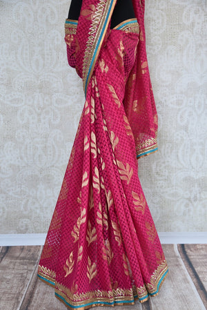 90a621 Traditional embroidered saree for sale online in USA. The jute pink Banarasi saree with golden leafy pattern on the body comes with a beige, embroidered raw silk designer blouse. This saree makes for the perfect Indian outfit to wear at small wedding function.