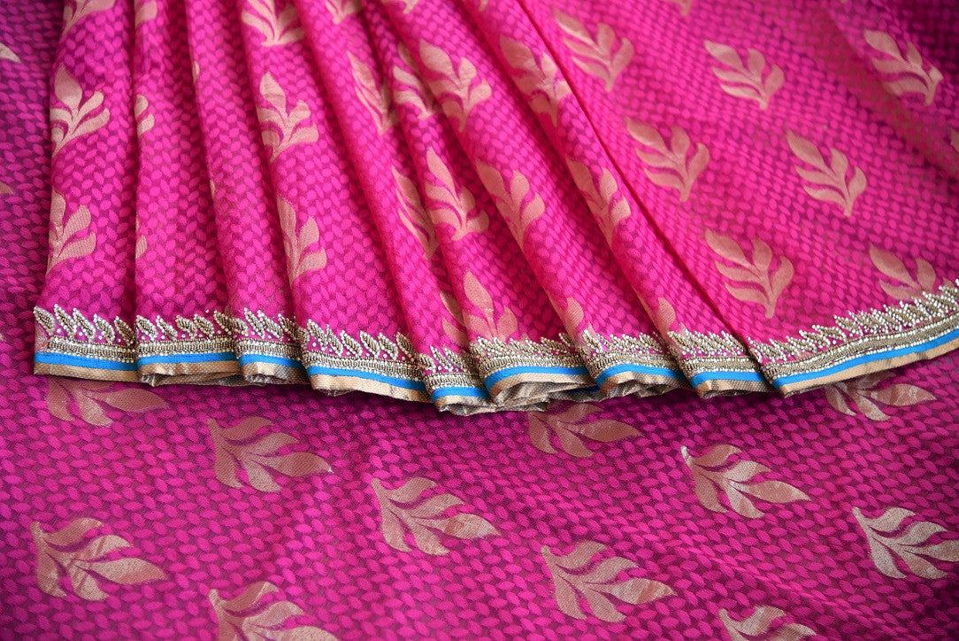 90a621 Traditional jute Banarasi embroidered saree for sale online in USA. The pink saree with golden leafy pattern comes with a beige, embroidered raw silk designer blouse. This saree makes for the perfect Indian outfit to wear at wedding functions and festivities.