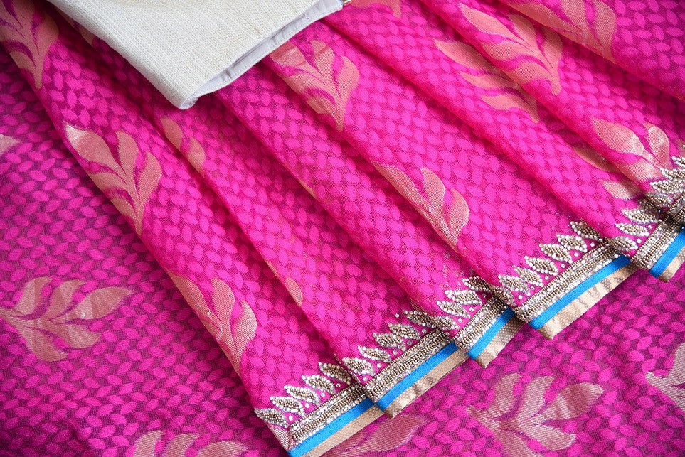 90a621 Embroidered pink saree for sale online at Pure Elegance in USA. The jute Banarasi saree with golden leafy pattern comes with a beige, embroidered raw silk designer blouse. This saree makes for the perfect Indian outfit to wear at small wedding function.