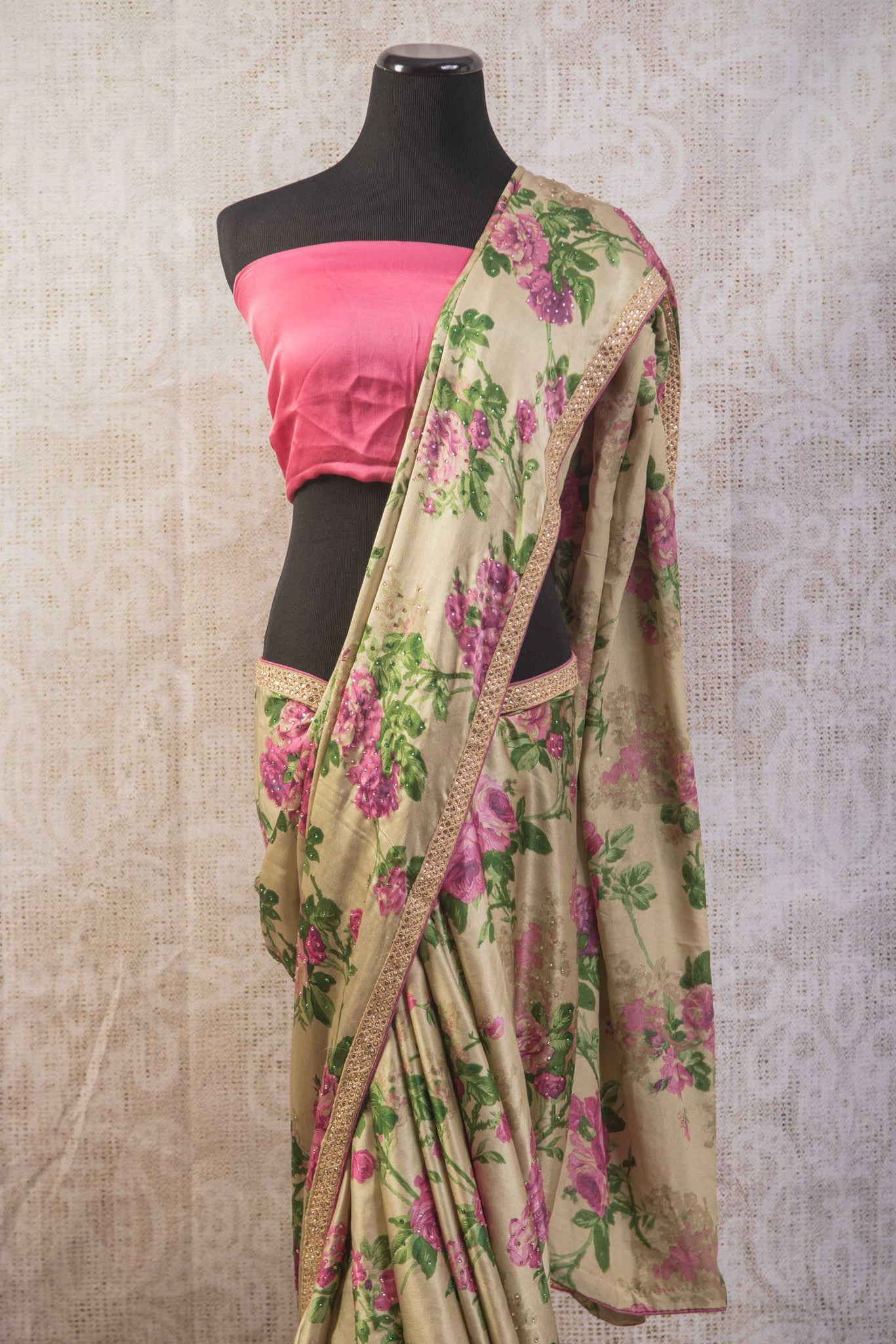 90a681 This floral saree available online at our Indian clothing store online in USA is a stunner. This beige satin crepe saree with purple and green rose print is an ideal party saree to have in your ethnic wear wardrobe.