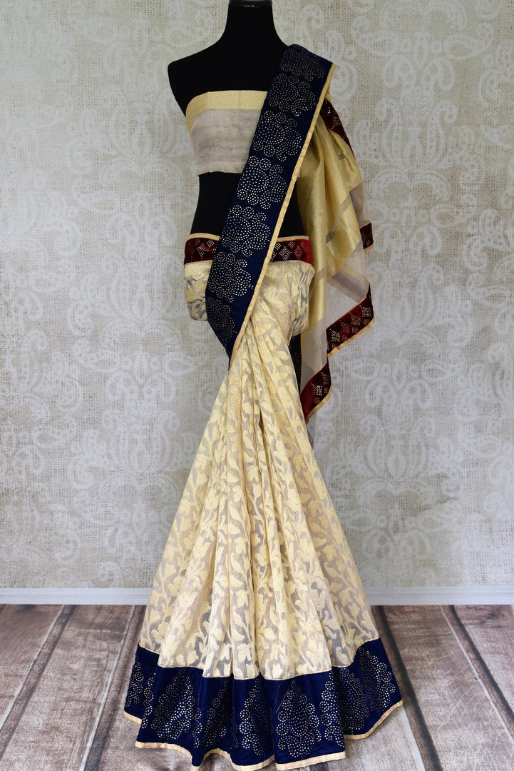 Shop cream net saree online in USA with blue stone work border. Shop the latest Indian women clothing and designer sarees for weddings and special occasions from Pure Elegance Indian clothing store in USA.-full view