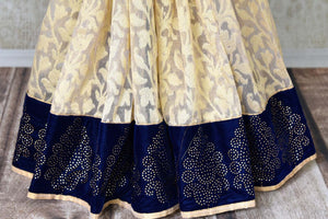 Shop cream net saree online in USA with blue stone work border. Shop the latest Indian women clothing and designer sarees for weddings and special occasions from Pure Elegance Indian clothing store in USA.-pleats