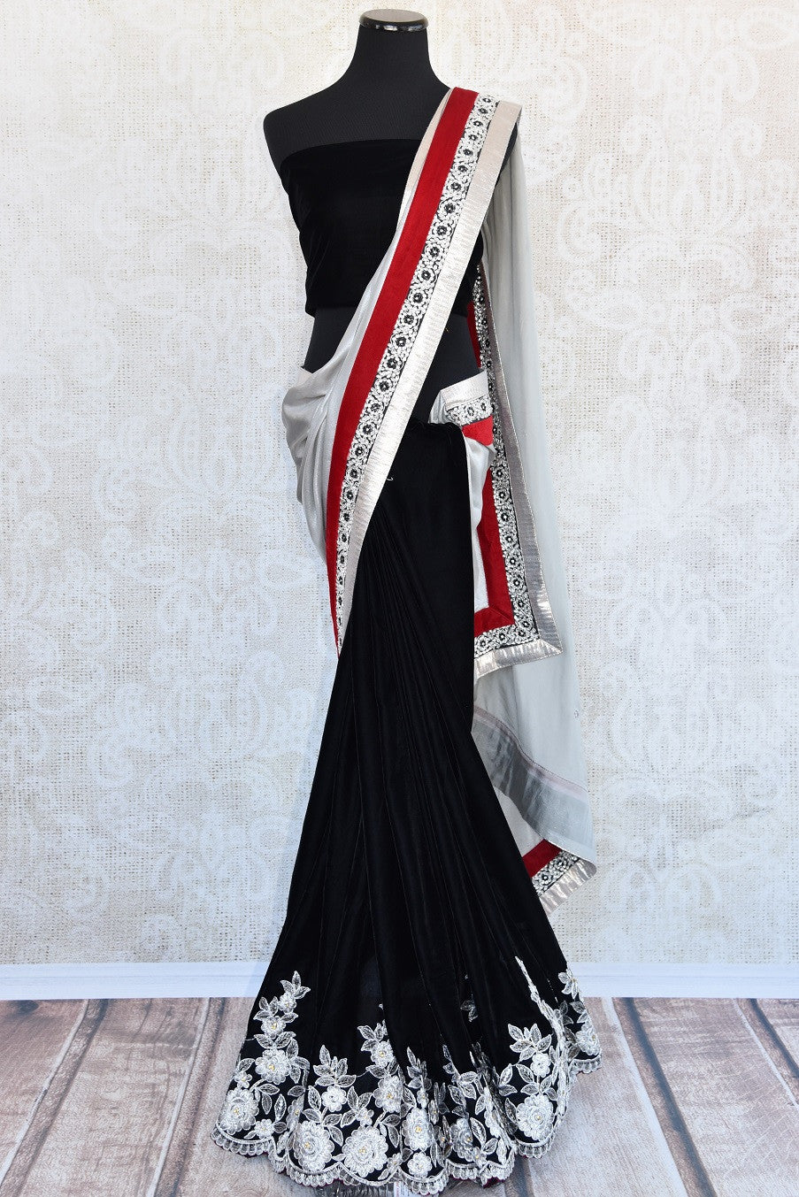 90A885 Black velvet saree with red and white border trims. This beautiful party wear saree is a must-have in your Indian clothing collection. The saree has floral design at the bottom and is available online in USA at Pure Elegance.