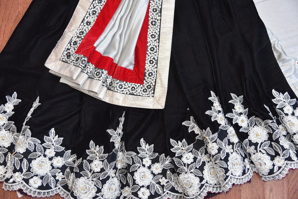 90A885 Black velvet saree with red and white border trims, that's a must-have in your Indian clothing collection. The party wear saree with floral pattern at the bottom is available online in USA at Pure Elegance.