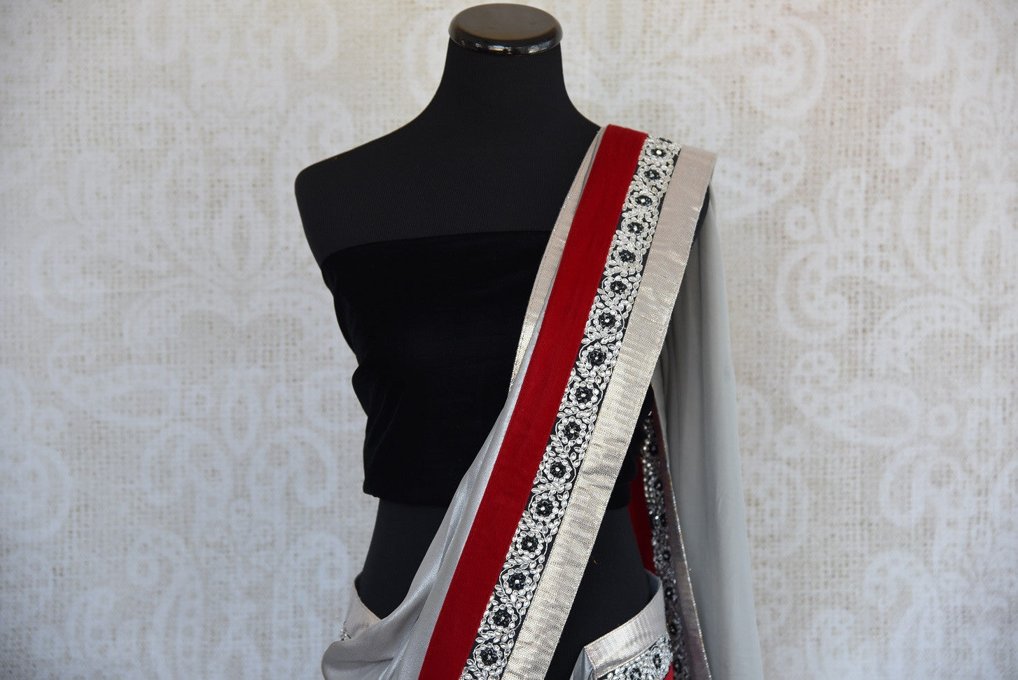 90A885 Black velvet saree with red and white border trims. This beautiful party wear saree with a floral pattern is a must-have in your Indian clothing collection and is available at Pure Elegance - our India wear store in USA.