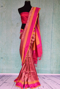 90a900 Pink Banarasi saree with a pop of orange that makes for a timeless Indian outfit. Buy this traditional saree at our Indian wear store online - Pure Elegance in USA and get ready to have all eyes on you wherever you go!