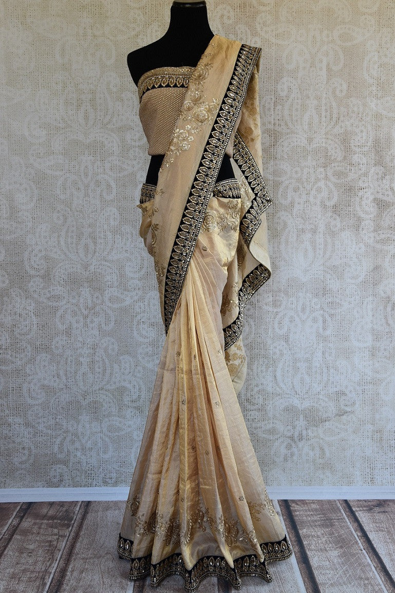 90A949 Exquisite white, black and gold saree online at Pure Elegance that's a timeless ethnic outfit. The embroidered tissue silk sari is a lovely pick for Indian wedding receptions and parties.