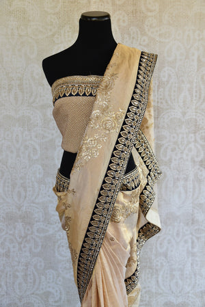90A949 Gorgeous white, black and gold saree online at Pure Elegance that's a timeless ethnic outfit. The embroidered tissue silk sari is a fabulous pick for Indian wedding sangeet functions, receptions and parties.