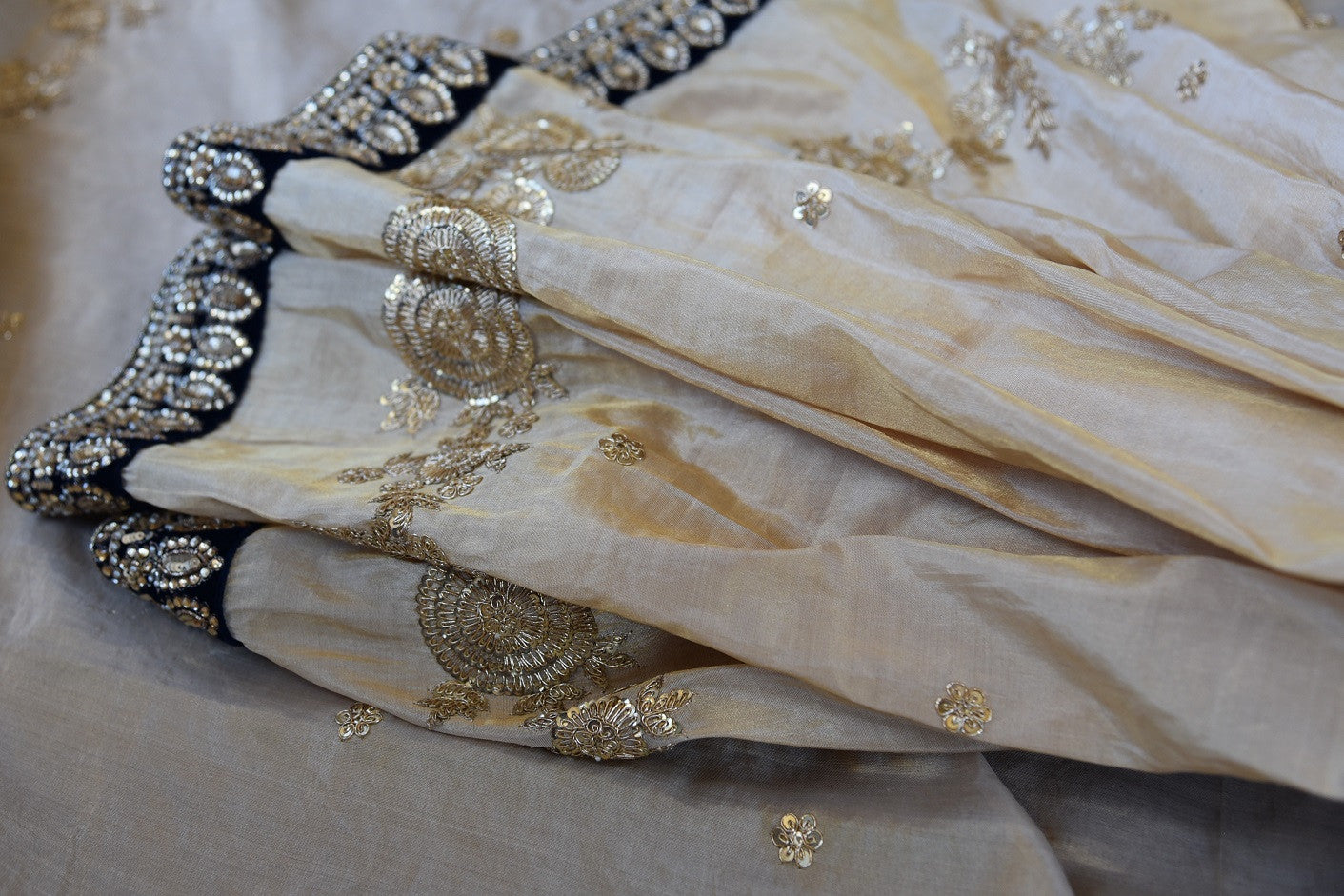 90A949 Exquisite white, black and gold saree online in USA at our Indian clothing store Pure Elegance. The embroidered tissue silk sari is a great pick for ethnic wedding functions and parties.