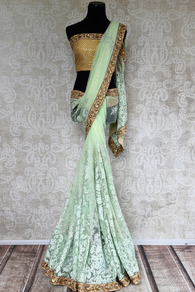 Buy Pure Elegance light green net embroidered saree with golden borders and golden blousepiece. Perfect Indian attire for any occasion this summer. - full