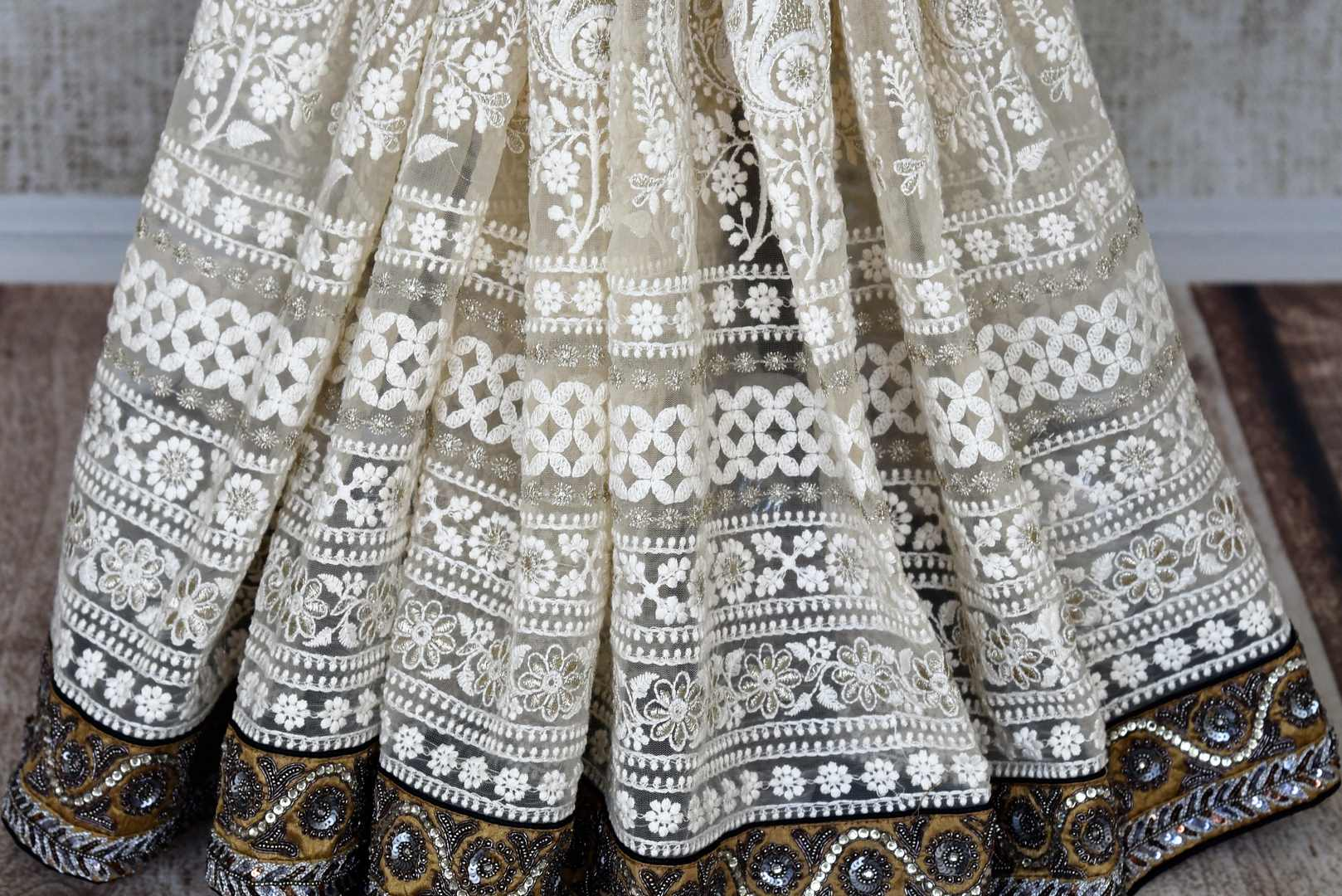 Shop off-white and black half n half embroidered net sari online in USA from Pure Elegance. Make your ethnic style perfect with a range of exquisite Indian designer saris, embroidered sarees, handloom saris available at our exclusive Indian fashion store in USA and also on our online store. Shop now.-pleats