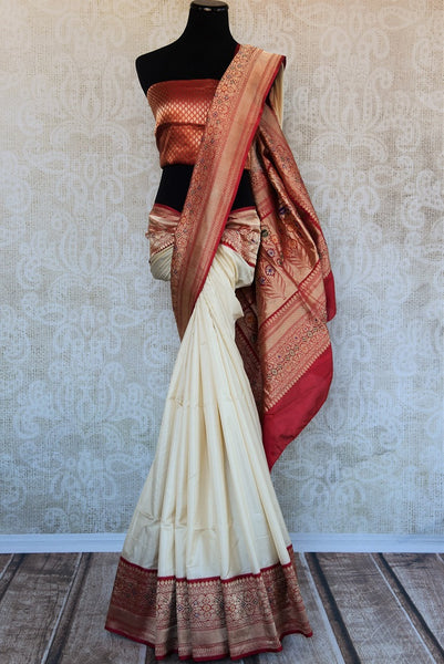 90B240 Traditional off white Banarasi silk saree with red and golden border. This saree available online at Pure Elegance is ideal for Indian wedding functions and receptions. This one is an eternally alluring style.