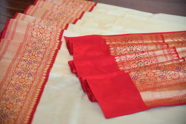 90B240 Off white traditional Banarasi silk saree with red and golden border. This saree available online at Pure Elegance is ideal for Indian wedding functions and receptions. This one will be a lovely addition to your Indian clothing wardrobe.